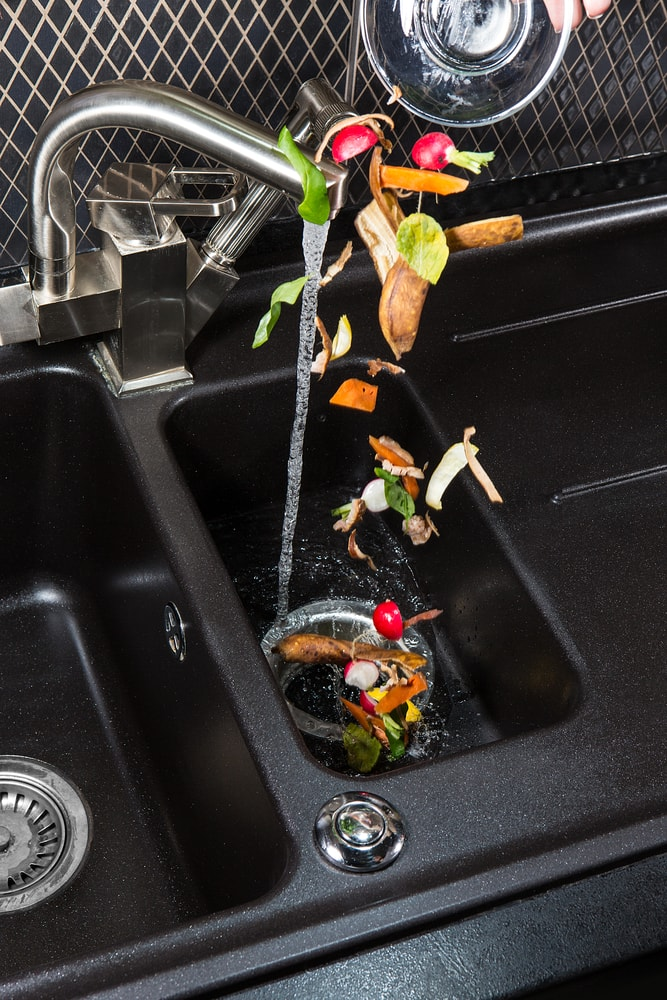 Food scraps being poured into a garbage disposal