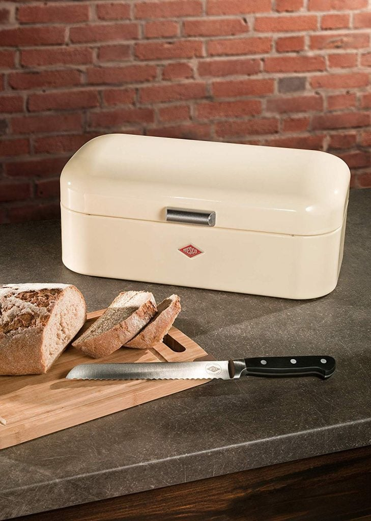 Fresh cut bread next to metal bread box